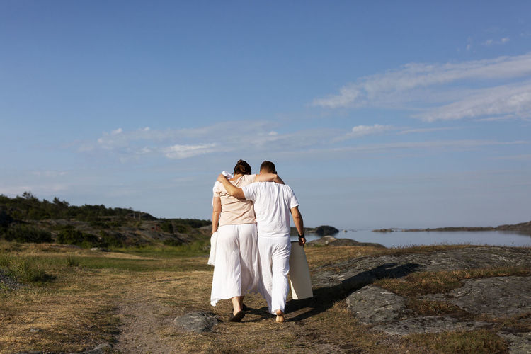 Rear view of couple standing against sky