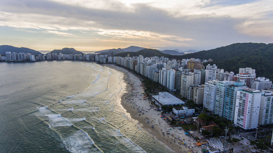 Panoramic view of beach and buildings against sky during sunset