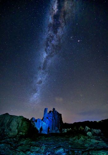 Scenic view of rock formations against star field