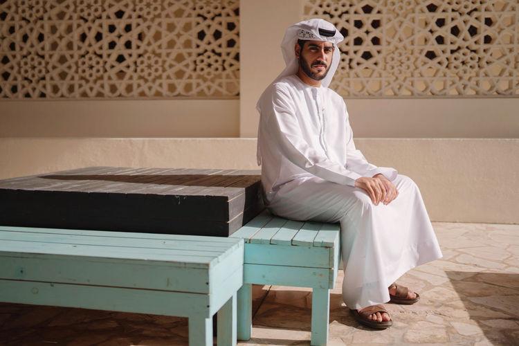 Portrait of arab man wearing dishdash kandura sitting down in a traditional bench