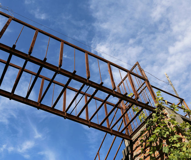 ancient suspended bridge of rusted iron outdoors and blue sky and clouds Catwalk Danger! Dangerous Animals Footbridge Hazardous Iron RISK Rust Suspended Architecture Bridge - Man Made Structure Built Structure Danger Dangerous Footbridge Crossing Low Angle View Outdoors Passage Pathway Rusty Sky Suspended Bridge Suspended In Air Walkway