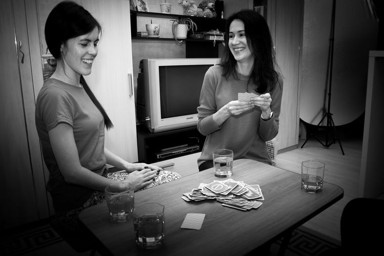 Lifestyles Indoors  Playing Cards Game People Friends Young Games Group Card Table Sitting Together Fun Party Adult Happy Weekend Friendship Hobbies Home White And Black W&B