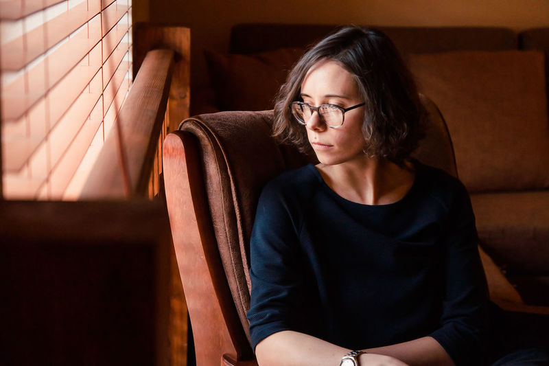 Woman looking away while sitting on chair at home