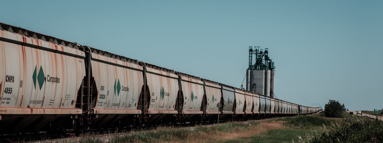 transportation, train - vehicle, day, clear sky, freight transportation, outdoors, no people, industry, architecture, built structure, factory, sky