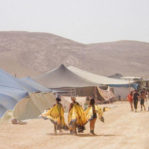 People enjoying in desert against sky