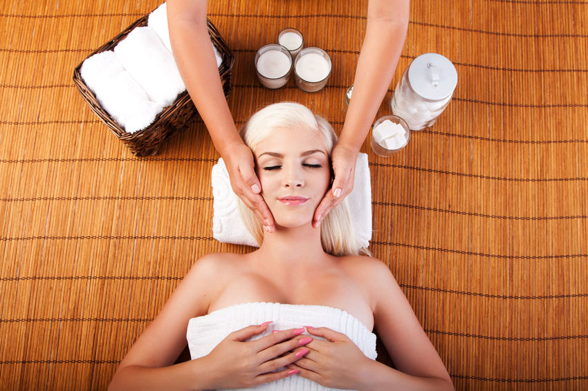 beautiful woman at spa getting relaxation massage. Bamboo Bodycare Candles Face Facial Female Happy Laying Luxury Massage Pampering Relaxation Serene Spa Therapy Towels Wellness Woman