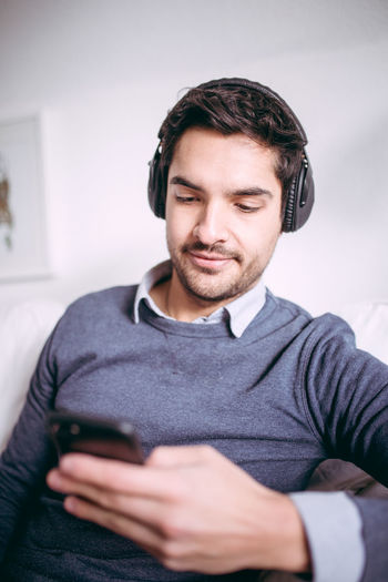 Young man is holding smartphone in his hand with headphones Casual Clothing Close-up Communication Connection Day Front View Holding Indoors  Leisure Activity Lifestyles Mobile Phone One Person People Portable Information Device Real People Smart Phone Technology Using Phone Wireless Technology Young Adult Young Men