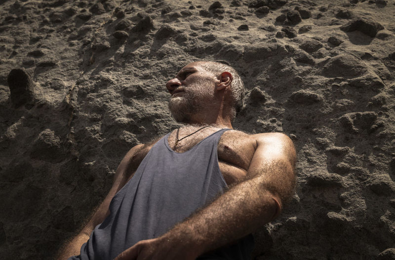 Portrait of adult man in tank top on beach against rock  in summer