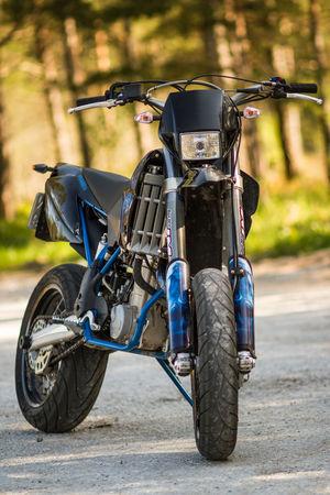 Husaberg motard motorcycle parked in front of green forest Husaberg Motard Motorcycle Off-Road Parked Superbike