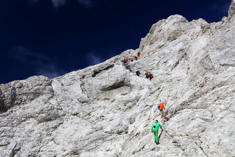 Low angle view of people on cliff against mountain