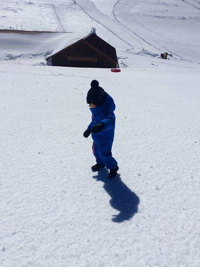 Full length of boy walking on snowy field