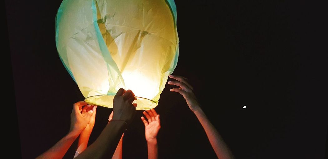 Cropped hands of people holding illuminated paper lantern against sky at night