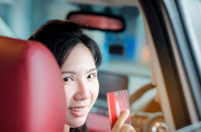 Happy woman thai sitting inside her new car showing credit card, Women Asia Portrait Headshot One Person Lifestyles Leisure Activity Real People Red Young Women Young Adult Women Holding Focus On Foreground Indoors  Adult Sitting Food And Drink Front View Seat Beautiful Woman