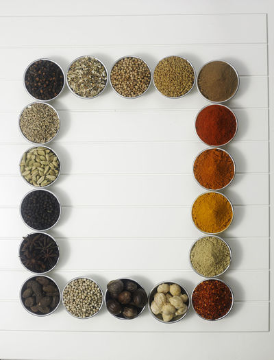 arrangement of spices on the white background Chili Pepper Choice Assortment Candlenut Cardamom Cinnamon Condiment Coriander Cumin Directly Above Ground - Culinary Group Of Objects Herbivorous High Angle View Ingredient No People Nutmeg Paprika Season  Spice Still Life Table Turmeric  Variation Variety