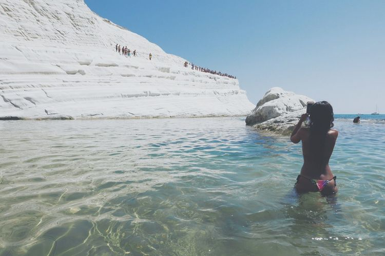 Rear view of woman in sea taking photo with smartphone
