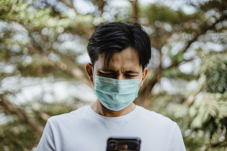 Man using mobile phone while wearing mask against trees
