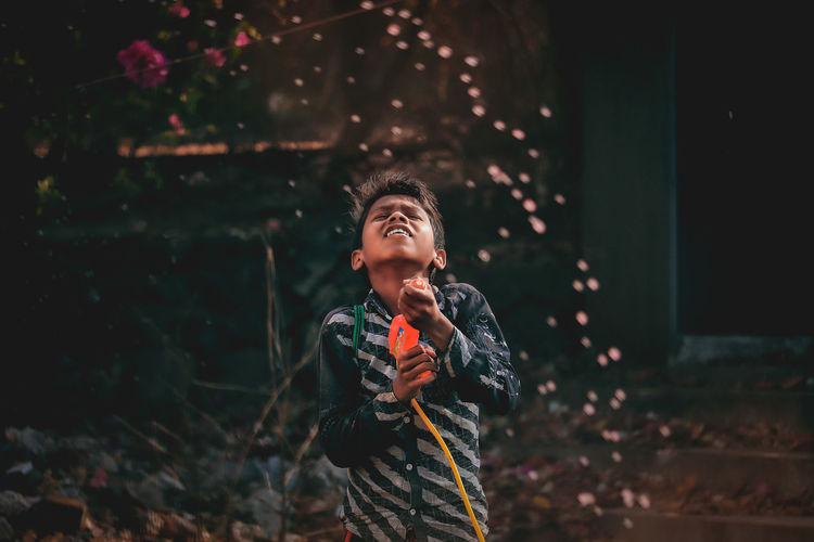 Boy holding squirt gun while standing outdoors