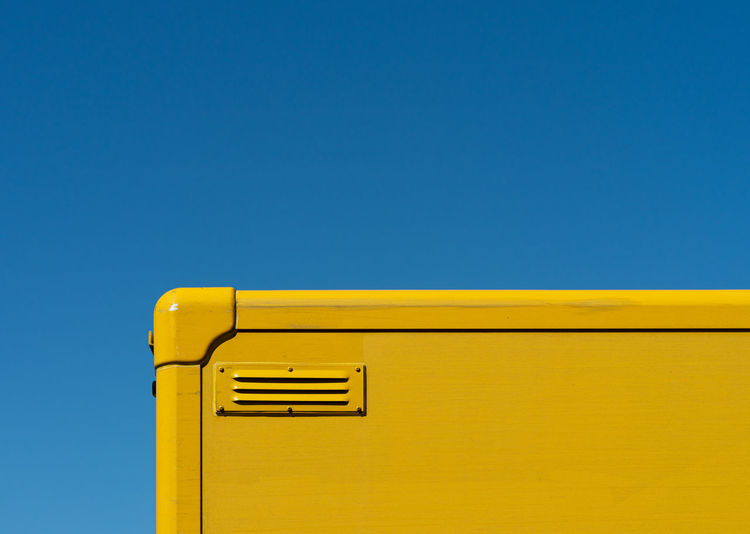 Low angle view of yellow container against clear blue sky