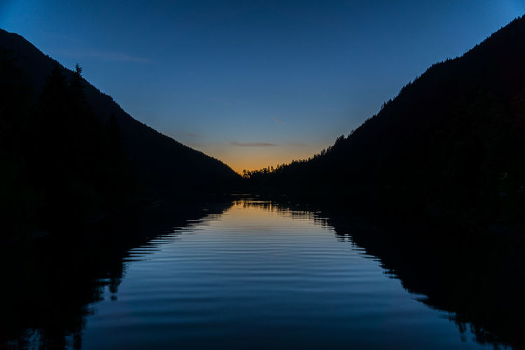 Scenic View Of Lake By Silhouette Mountains Against Sky