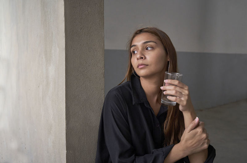 Portrait of a beautiful young woman drinking glass against wall