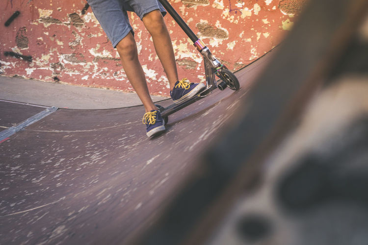 Low section of boy riding push scooter at skateboard park