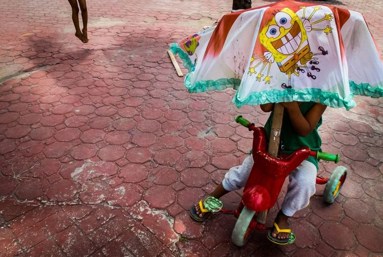 Close-Up Of Child Sitting On Tricycle Covering With Umbrella