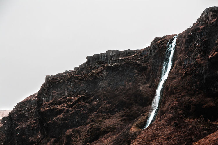 Low angle view of rocky mountains with small waterfall against cloudy sky