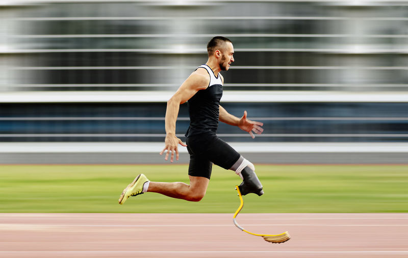 Full length of handicap man running on track