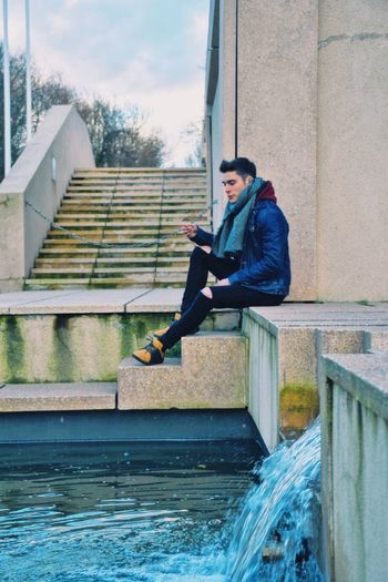 Full length side view of man sitting by canal in city