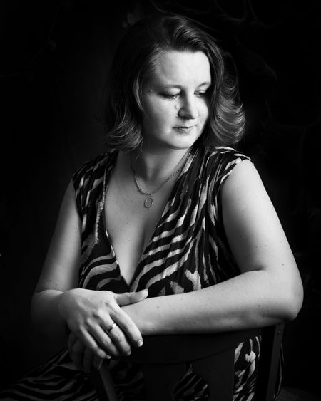 Thoughtful woman sitting on chair against black background