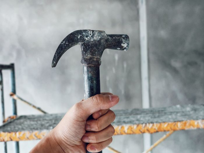 Cropped Hand Of Worker Holding Hammer Against Wall