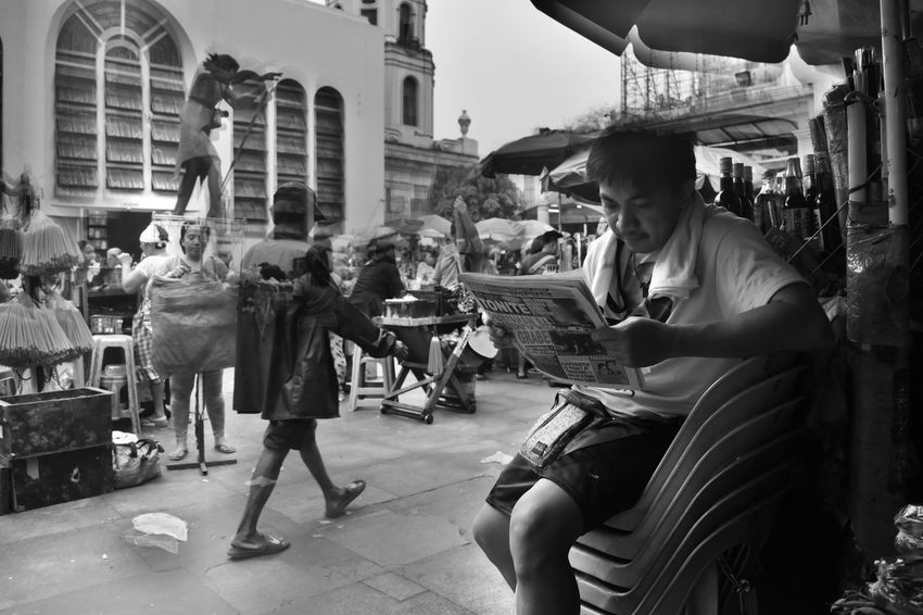 This man reading his daily news in a noisy morning environment during a Sunday mass reflects on how Quiapo is being left out from the rest of the major playing cities of the Philippines' capital region. It is tantamount to staying at its own pace as the rest its neighbors boom in progress. Adult Black And White Building Exterior City Customer  Day Large Group Of People Lifestyles Manila Market Outdoors People Philippines Photojournalism Quiapo Real People Street Photography Young Adult
