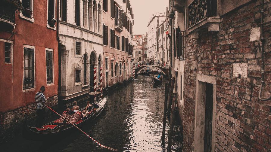 People sailing in gondola amidst buildings