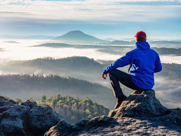 Man on the peak of rock. man sit with hand on knee with beautiful sunrise landscape. hiker is watch