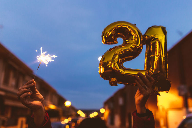 Man and woman couple holding gold foil balloons numeral 2021. new year celebration concept.