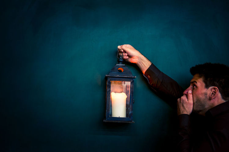 Man Holding Lantern With Candle By Blackboard