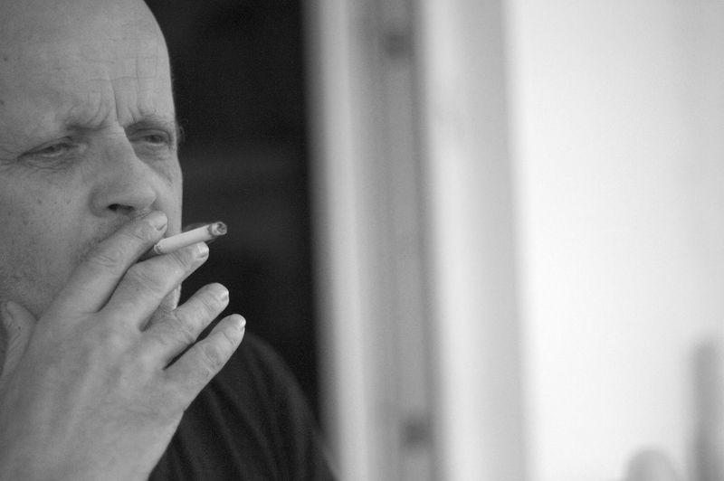 Man looking away while smoking cigarette