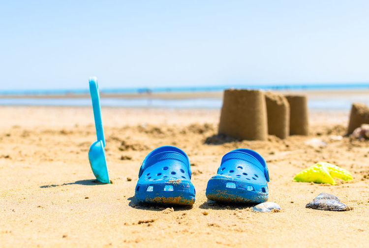 Blue shoes on sand at beach against clear sky