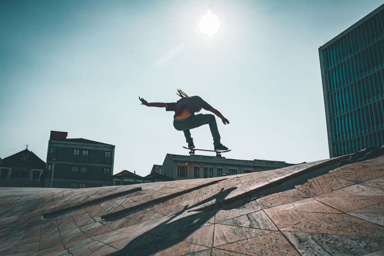 Low angle view of man jumping on built structure