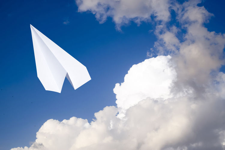 Low angle view of white bird flying against blue sky