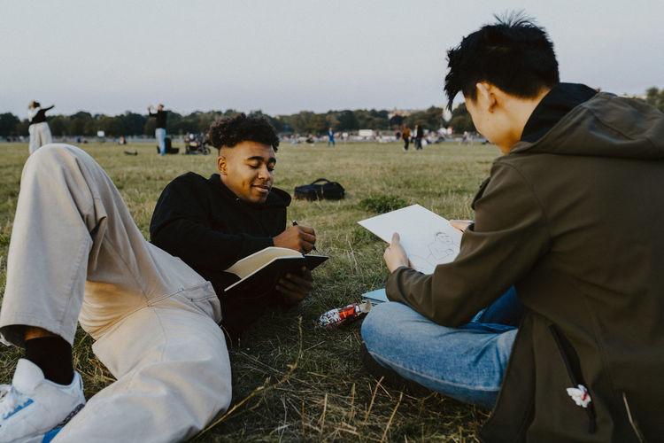 Men sitting on field