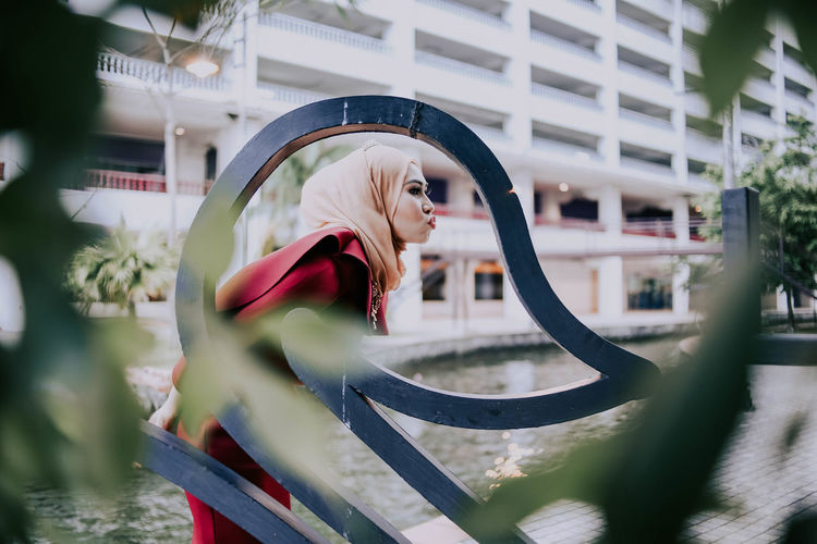 Woman with duck face framing duck Beautiful Duck Face Framing Adult Architecture Beautiful Woman Blond Hair Built Structure Clothing Day Duck Female Hair Hairstyle Interesting Pictures Leisure Activity Lifestyles One Person Real People Reflection Selective Focus Standing Women Young Adult Young Women