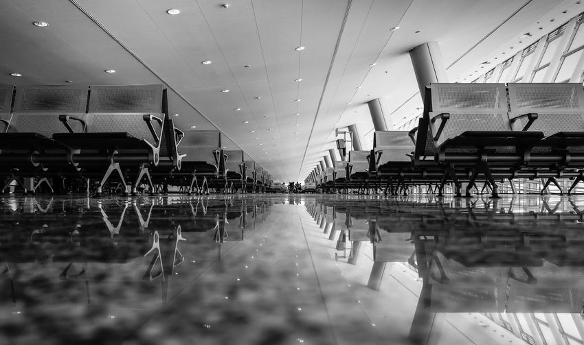 Seats reflection on tiled floor at airport departure area