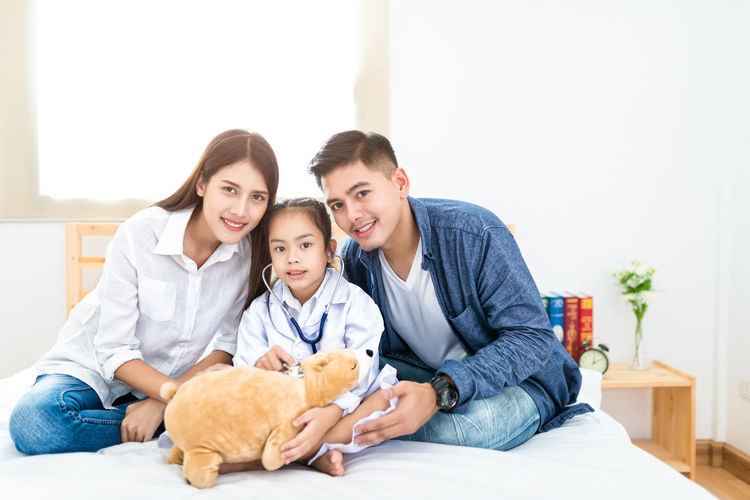 Little doctor, Cute little asian girl dressed like a doctor at home Family Happiness Home Learning Love Advance Child Childhood Daughter Education Family Females Furniture Future Group Of People Indoors  Males  Men Mother Parent Smiling Teddy Bear Togetherness Warmth Women