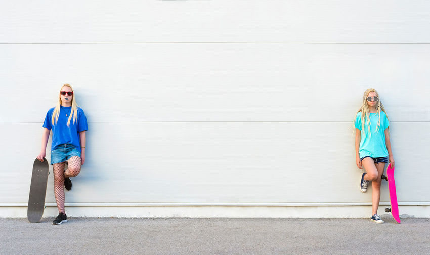 Portrait of women with skateboards standing against wall