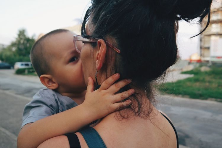 Baby Boy Kissing Mother On Street