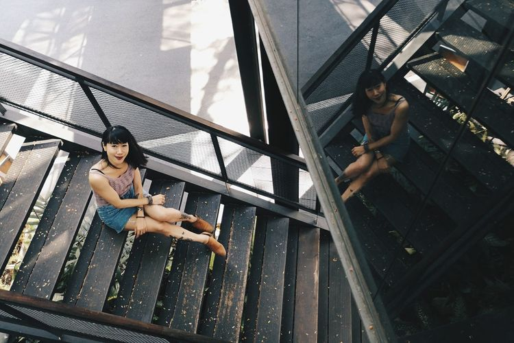 High angle portrait of mid adult woman sitting on steps