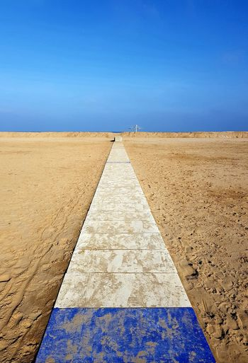 Diminishing Perspective Of Footpath On Beach Against Blue Sky