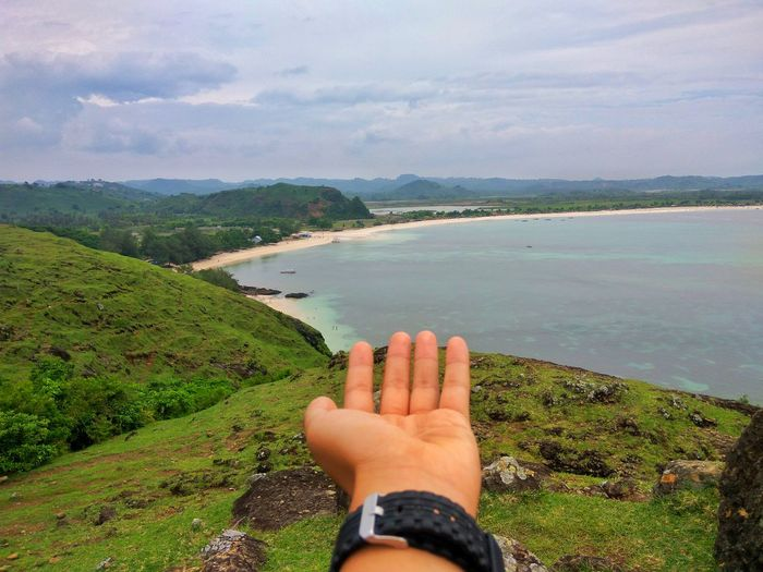 Cropped hand on mountain by sea against cloudy sky