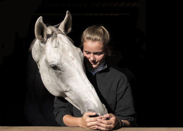 Young woman by horse against black background